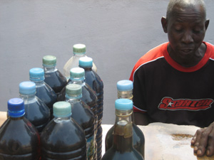 [Guinea] Selling petrol on the street in litre bottles serves the vendor with cash and the cash-strapped consumer with affordable quantities. [Date picture taken: 11/23/2006]