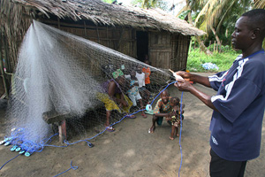 Waibite Amazi, a fisherman in Nigeria's troubled oil-rich delta region,  spreads out his net outside his homestead, Nigeria, 1 December 2006. Hostage-taking has become frequent in the Niger Delta and attacks on oil installations and personnel last year cu