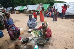 [Somalia] Women prepare food at an internally displaced persons camp in Arare, 12 km from Jamame, southern Somalia, 15 December 2006. Although humanitarian agencies have provided relief aid after the worst floods in 10 years, lack of proper sanitation and