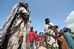 [Kenya] Women and children wait to be transferred to Dadaab's refugee camps at Liboi reception centre, along the Kenya-Somalia border in the remote eastern region of the country, 28 November 2006. The United Nations High Commissioner for Refugees dispat