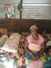 [South Africa] Phophi Sophie Makushu, 55, in her home in Sihlala Nge Nkani, in front of a picture of President Thabo Mbeki. [February 2006]