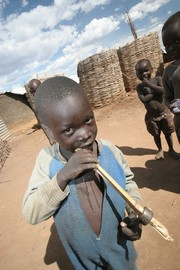 [Uganda] A young boy chews on a piece of sugar cane in Padibe internally displaced people's (IDP) camp in Kitgum District, northern Uganda. The camp is home to over 30,000 people displaced by the near two decade long rebellion against the Ugandan governme