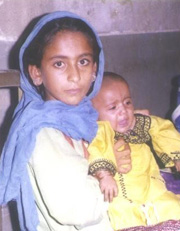[Pakistan] Sidra, aged 13, with her daughter born eight months ago. Sidra was married a year ago. [Date picture taken: 03/31/2006]