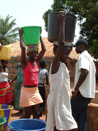 [Guinea-Bissau] Young girls carry water in buckets on their head in Bairro Militar, a poor district of Bissau where people get water from shared street taps. [Date picture taken: 05/29/2006]