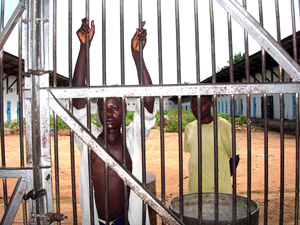 [DRC] Two prisoners in Osio prison wait behind bars for a second chance of freedom by the court of appeals in the Democratic Republic of the Congo, May 2006. After years of civil war and decades of unrest, the country's infrastructure has almost complet