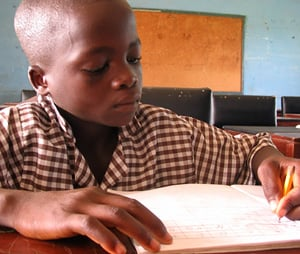 [Ghana] David, 10, doing school work at the shelter for rescued trafficked children in Accra, where he arrived in March. For two years he worked with a fisherman on Volta Lake. [Date picture taken: 06/29/2006]
