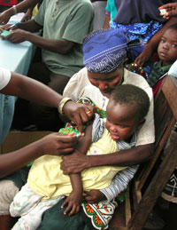 [Kenya] A child is vaccinated against measles at the GK Kibo Prison Camp, about 8 km from Kisumu city in western Kenya, one of the sites where the integrated measles, vitamin A, and mosquito net campaign was operating, 8 July 2006. The mass vaccination ca
