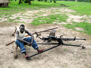 [Sudan] A young man from the White Army civilian defence force next to his heavy machine gun in Akobo, Jonglei State, South Sudan, July 2006. Some members of the White Army have resisted disarmament for fear of increased vulnerability to attack. Others do