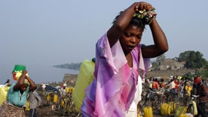 Women carry jerry cans of water at the Plage du Peuple, north Kivu, eastern DRC, 13 September 2006. Following a cholera outbreak in Goma earlier this year, UNICEF and OXFAM set up a project to provide people with safe chlorinated drinking water, which is