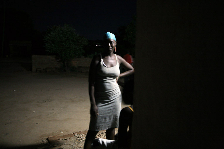 A sex worker stands outside a bar, March 2007. Alcohol and drug use can lower inhibitions, increasing the risk of HIV infection. However, some groups are especially vulnerable - most notably young women. The impact of HIV/AIDS has gone far beyond the hous