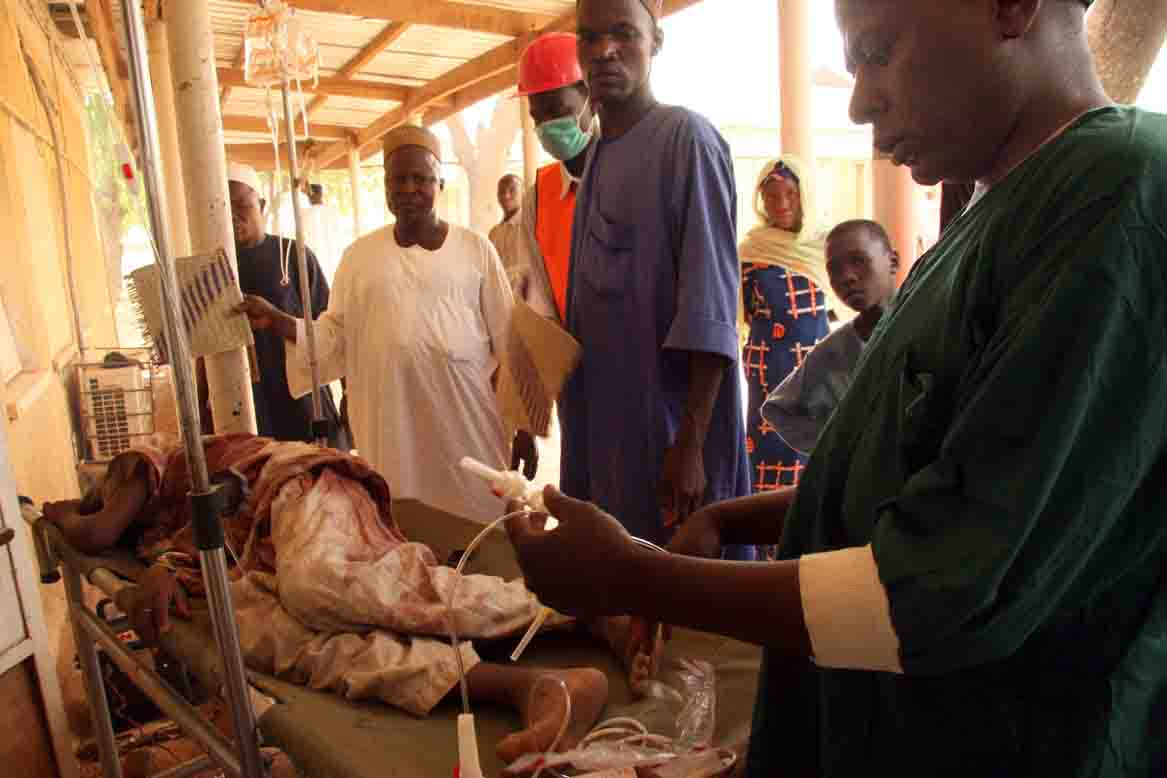 A young boy is tended to by doctors as he lies wounded at a health clinic in Daura, Katsina State, northern Nigeria, 21 April 2007. More than a dozen people were injured and at least two died in violent clashes in the northern town of Daura, home of oppos