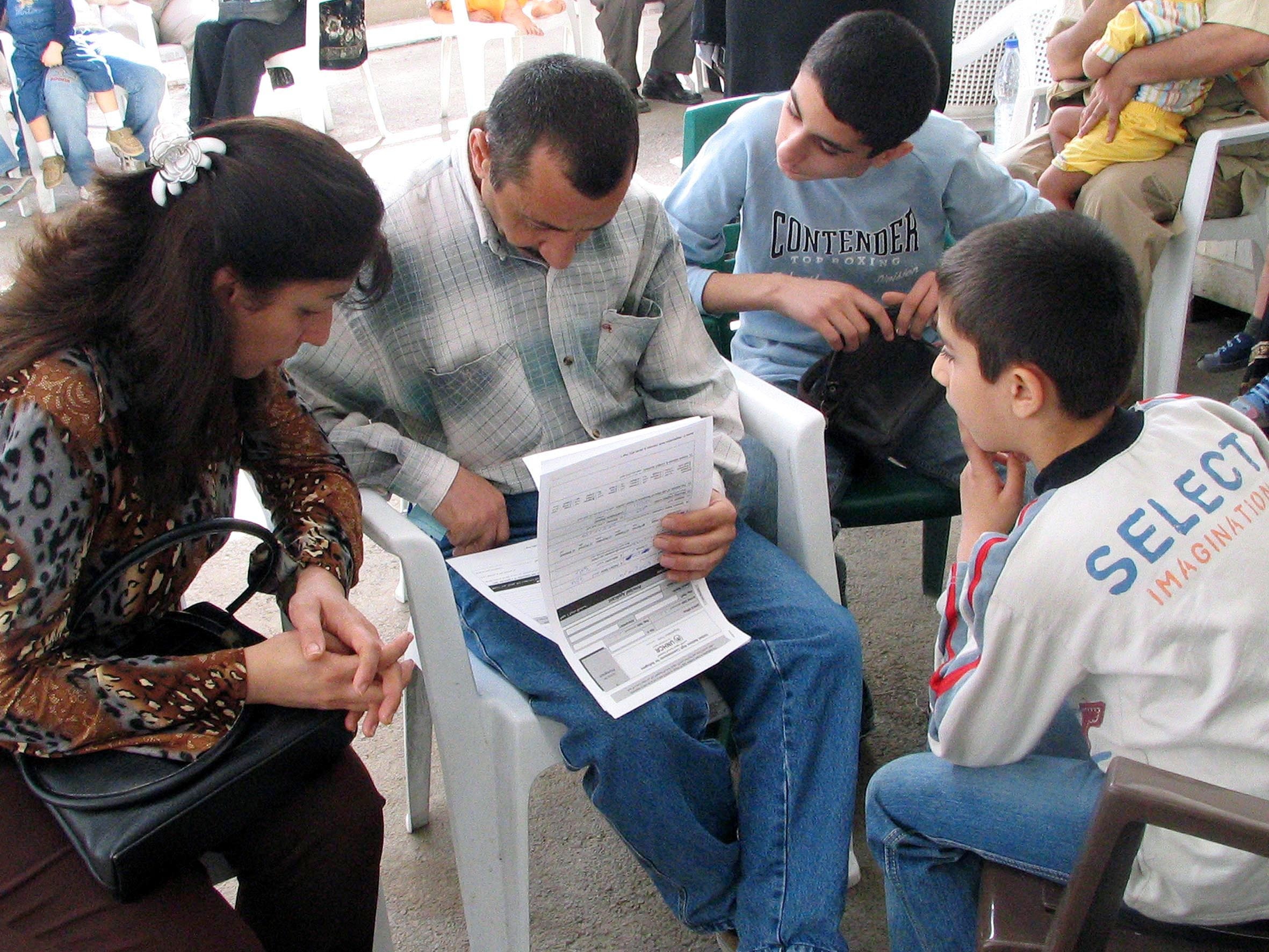 An Iraqi family fills out their form to register as refugees at the UNHCR's new centre outside Damascus.