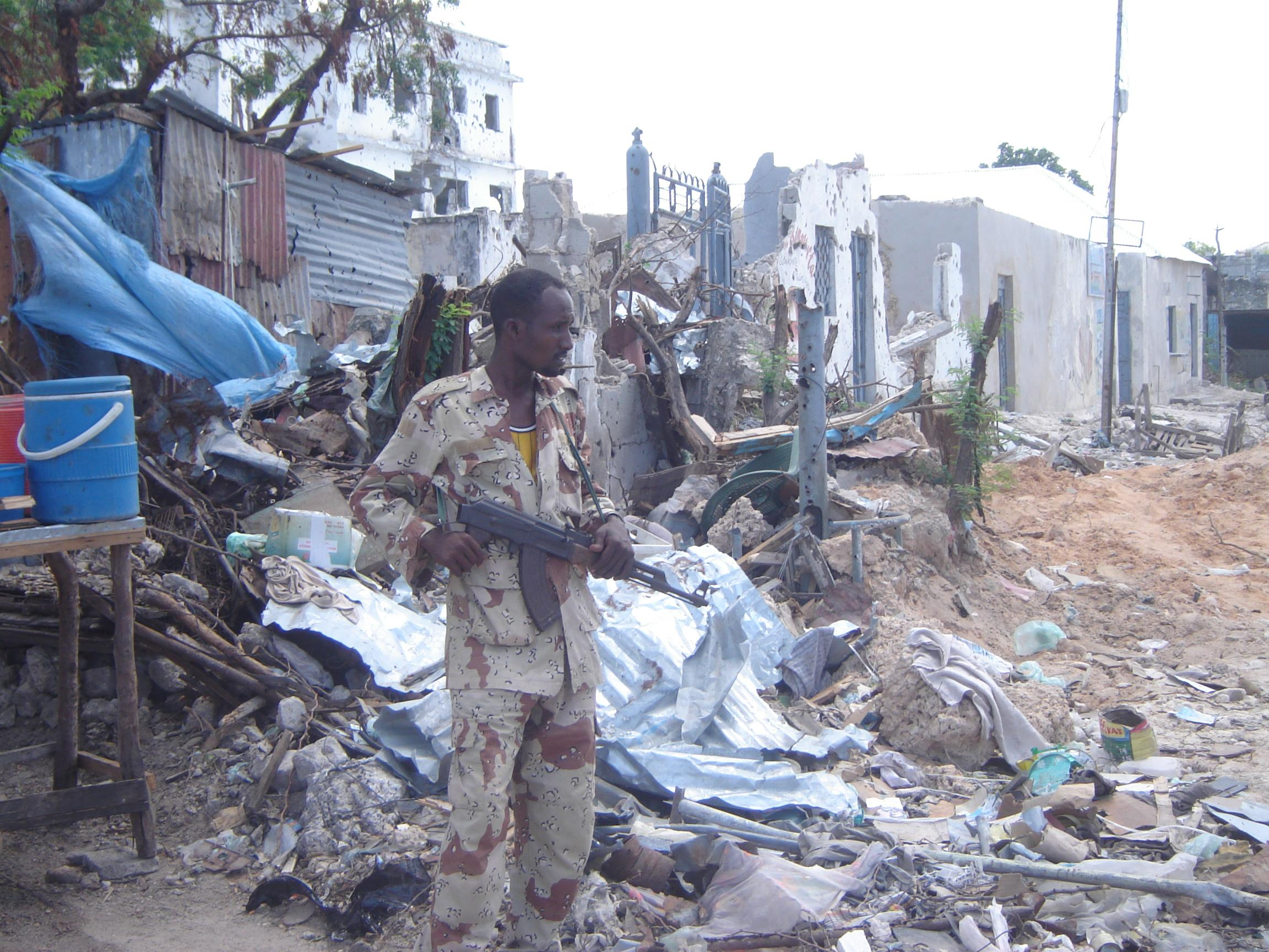 A Somali soldier near a building  destroyed in recent fighting between the government and insurgents, Mogadishu, Somalia, 22 May 2007. Most  displaced people cannot return home because their houses have been destroyed by mortar shelling, or because they c