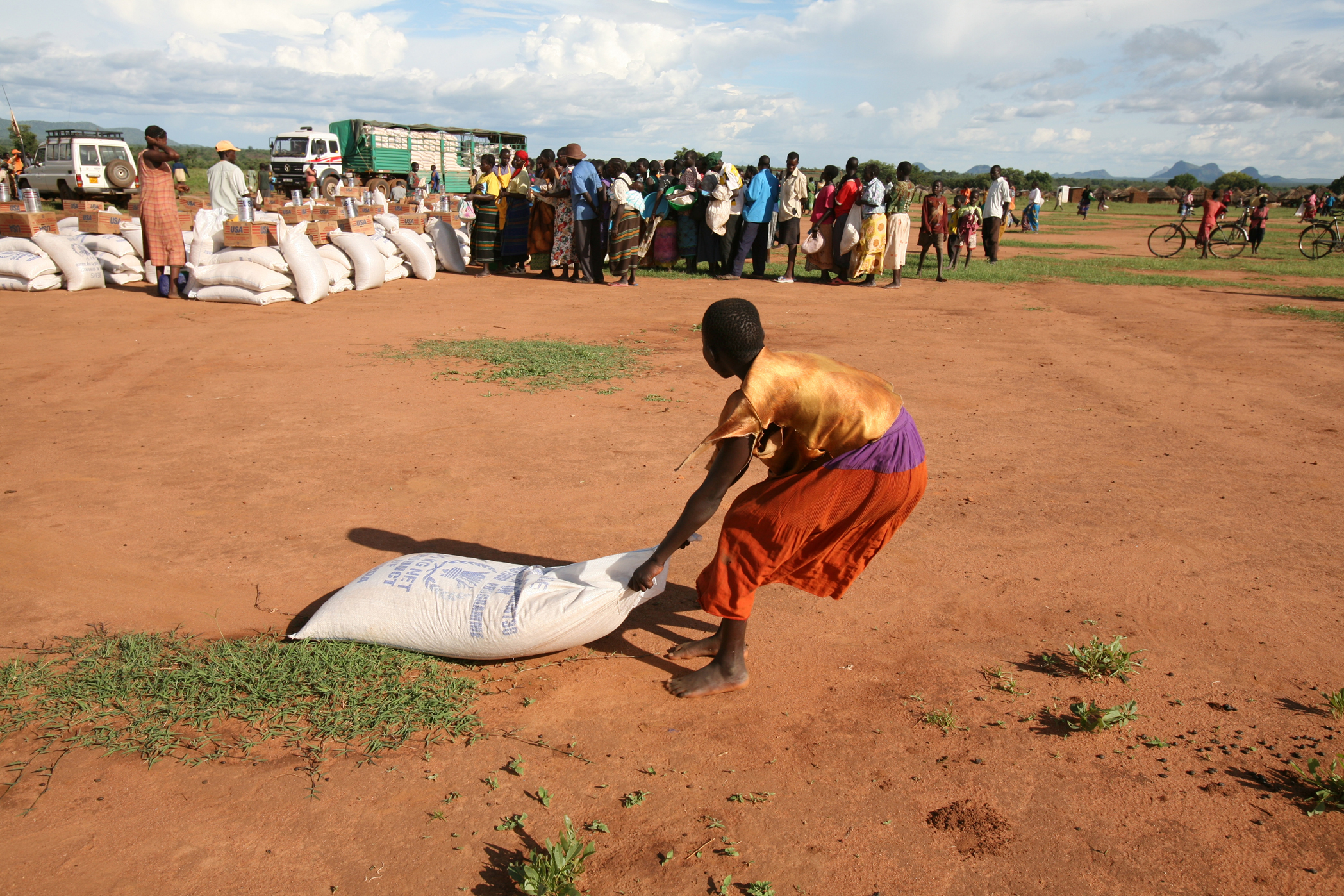 A young girl dragging a sack of food at the Oromi IDP camp, Kitgum District, northern Uganda, 18 May 2007. In April, WFP was forced to reduce the individual food aid package for the displaced to just 40 percent of the minimum daily energy requirement beca