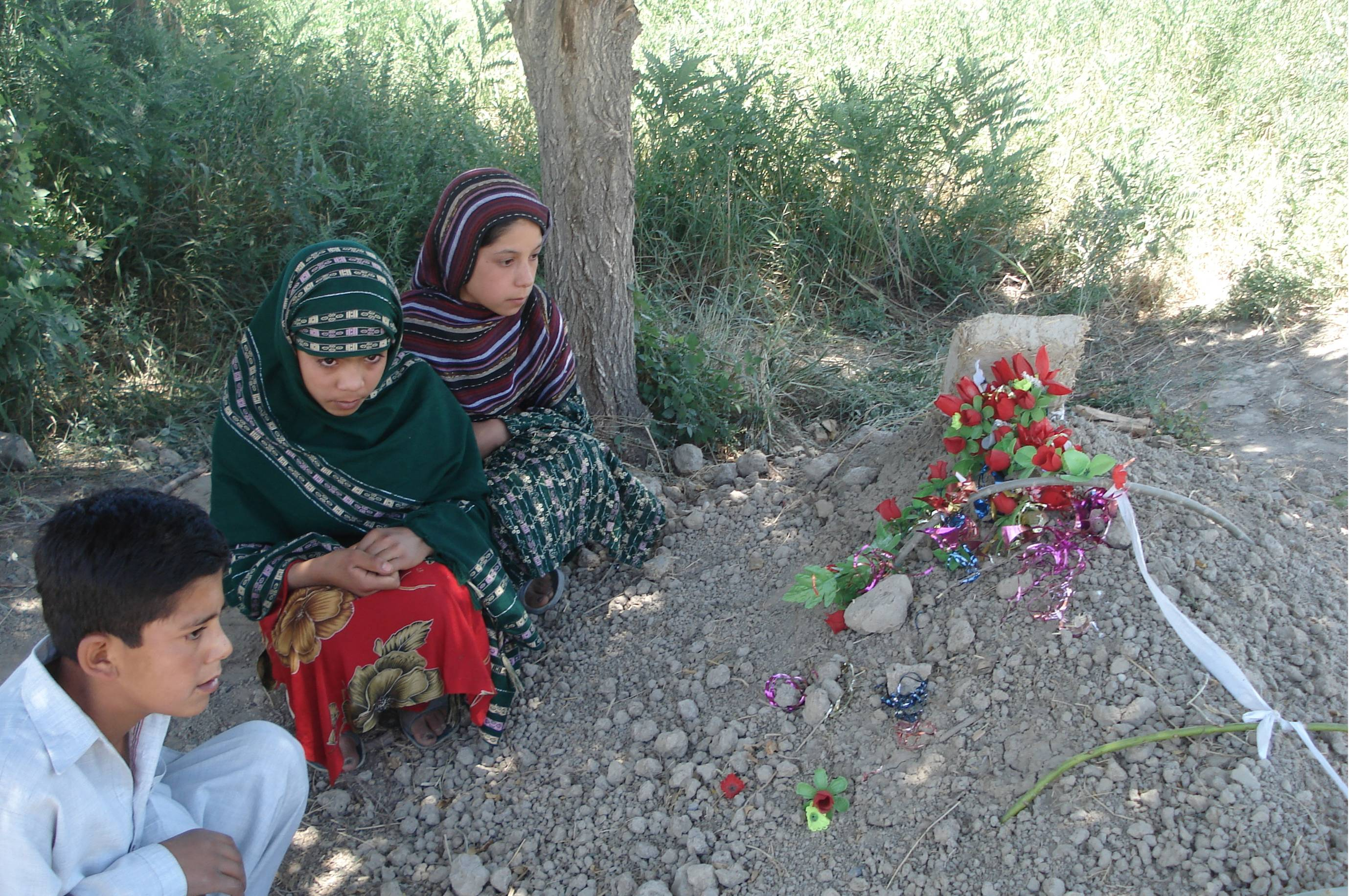 Children pray near the grave of 12-year-old Shukria who was killed in the shooting.
