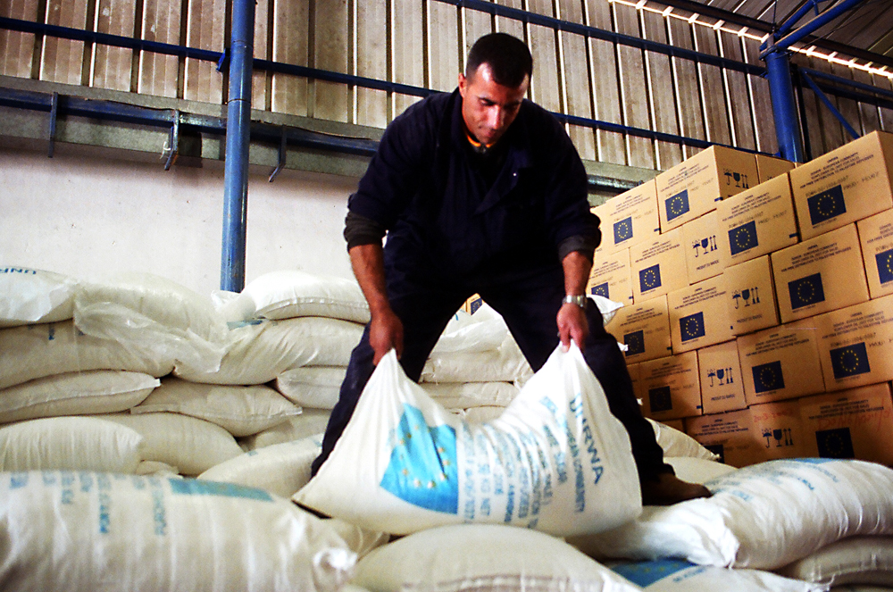 A UNRWA aid worker in a warehouse.