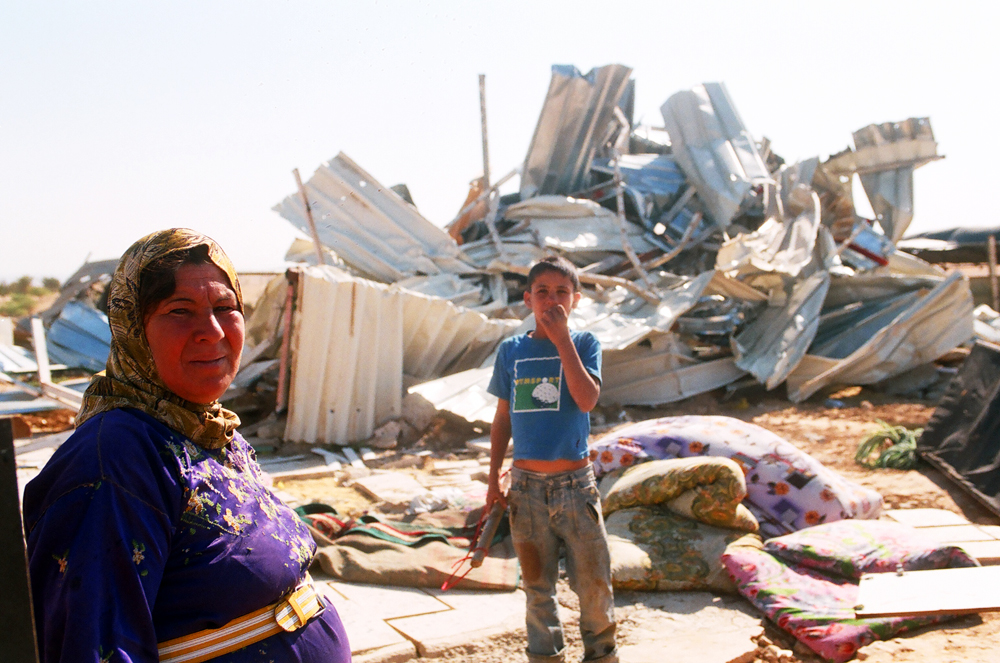 A woman and her child standing in front of their demolished home in Atir.
