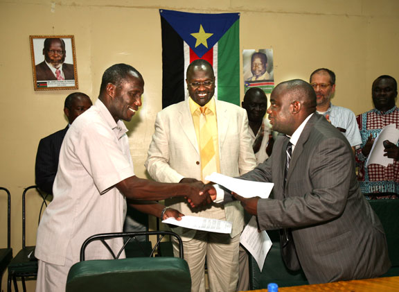 Ugandan government representative S. P. Kagoda (right) exchanges signed documents with Martin Ojul (left), leader of the LRA delegation, in the presence of Vice President of the Government of Southern Sudan Riek Machar (centre) in Juba, 29 June 2007.