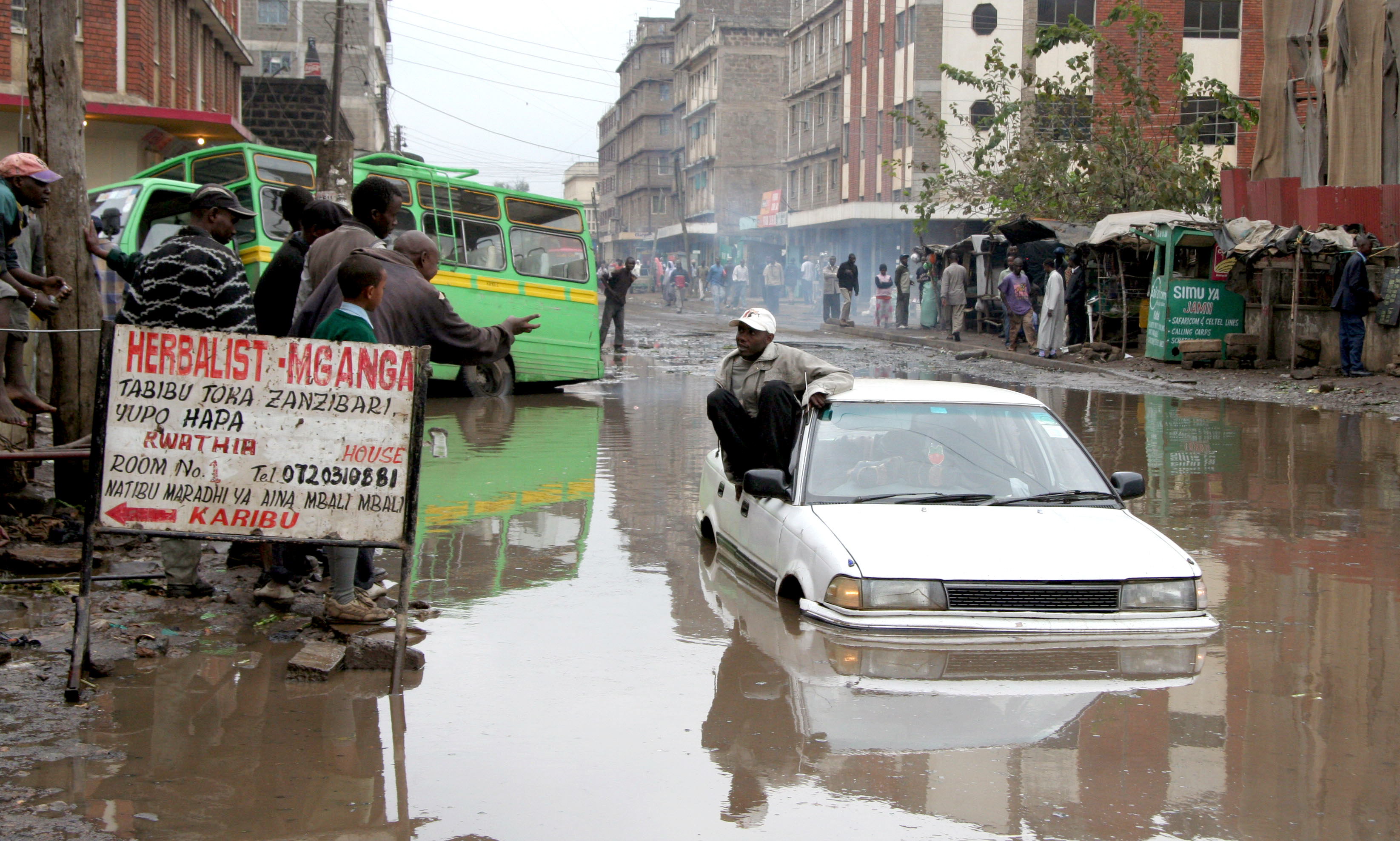 A motorist surrounded by water in the suburbs of Nairobi, Eastleigh area, July 2007. Deteriorating road condition due to poor maintenance coupled with bad weather conditions have left many Kenyan road a nightmare to motorists and other road users.