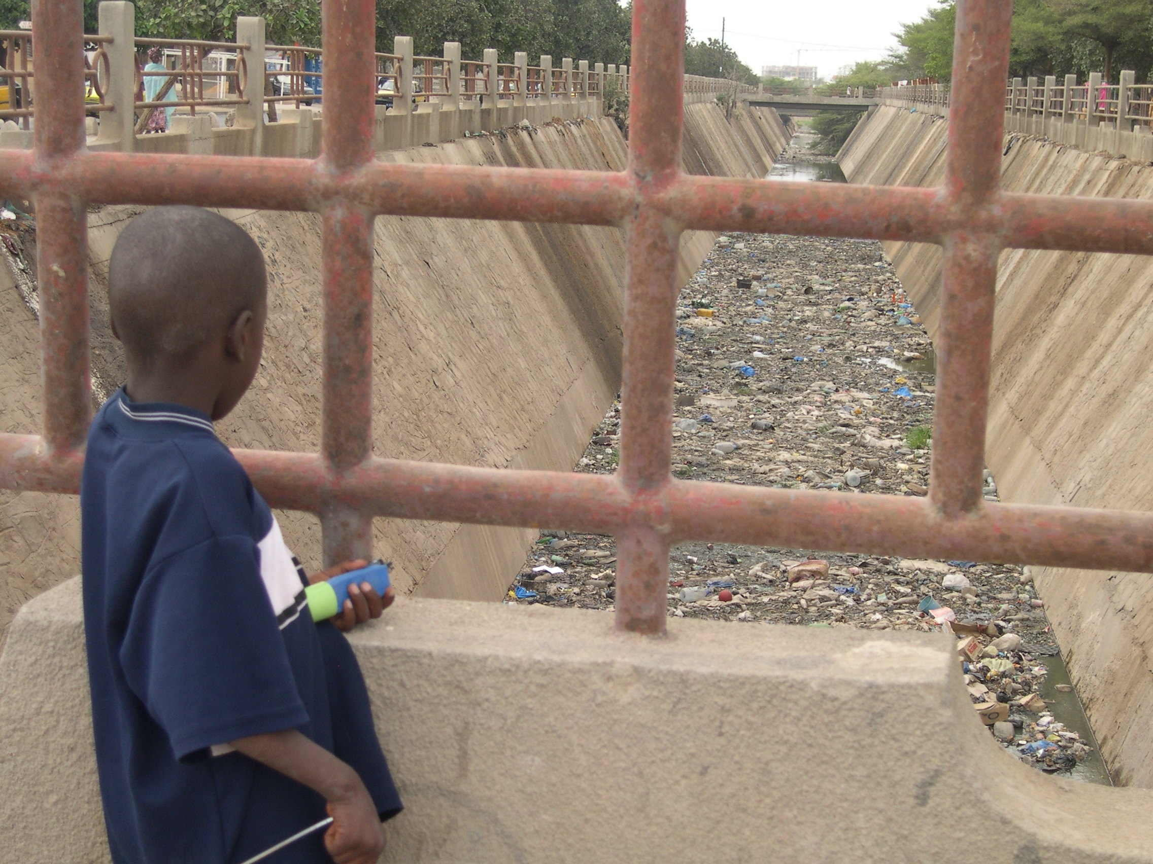 A neighbourhood child looks down at Canale 4, a channel meant for collecting rainwater.