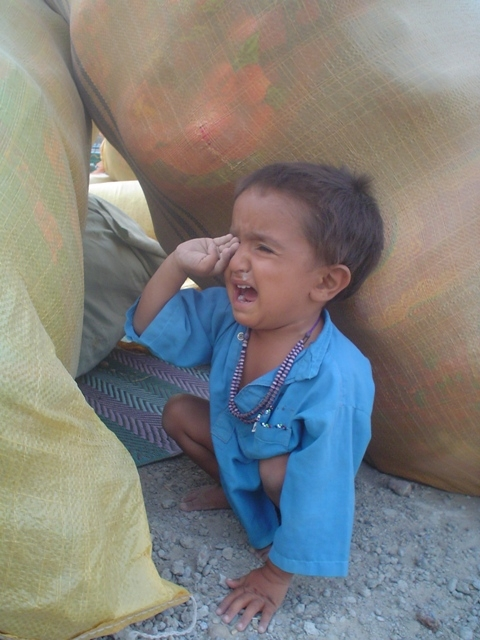 Squeezed between two sacks of household items, a displaced Afghan child cries in Helmand Province.