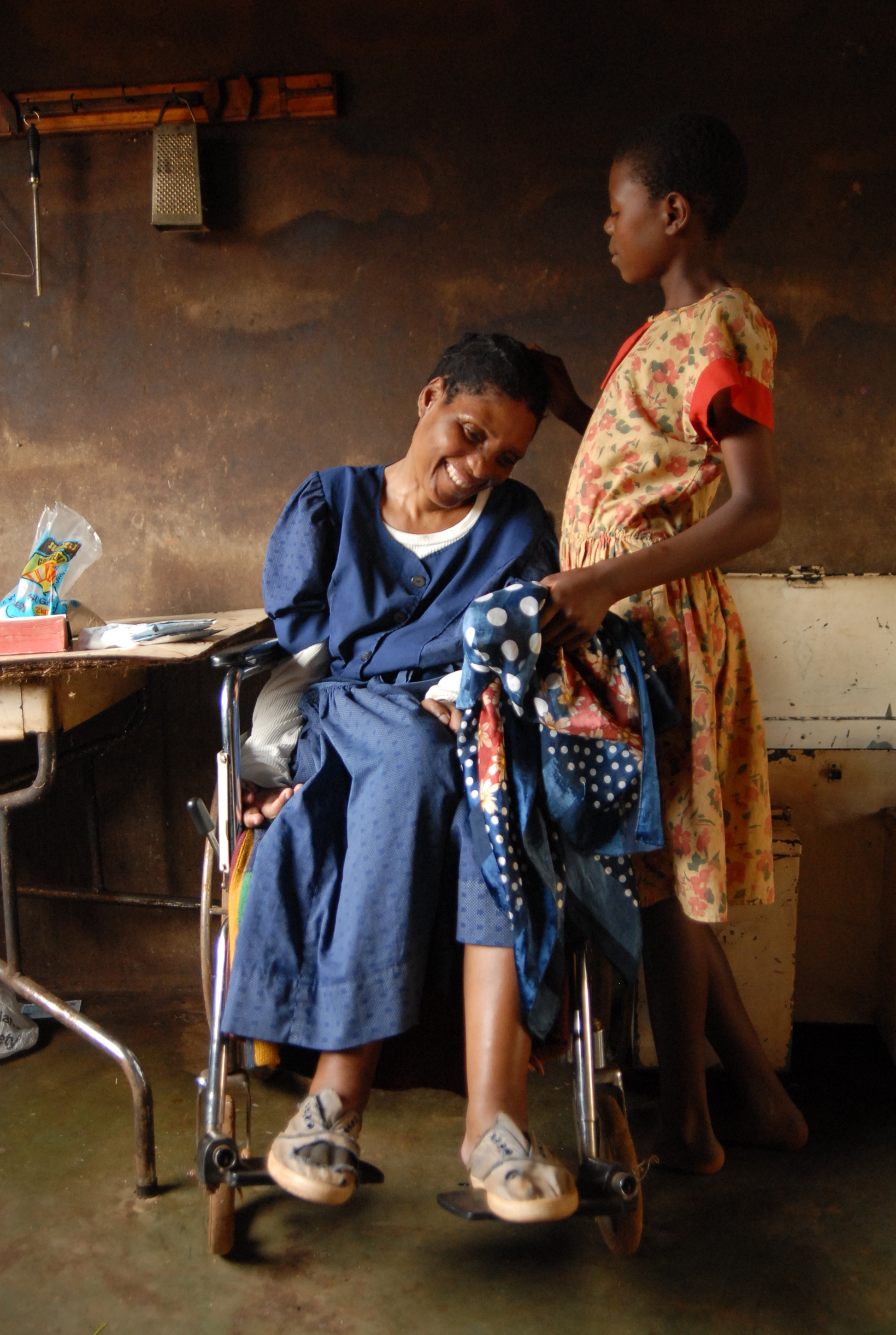 Fisiwe Malinga, 12, scratches her grandmother Zodwa Malinga's head. Wheelchair-bound after a stroke, she is unable to do anything for herself. Yet, six grandchildren are staying here with her. Several of them are orphans due to HIV/Aids and the rest were