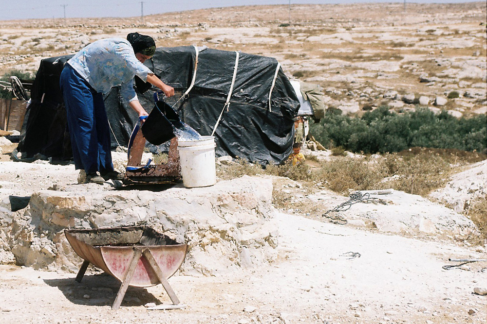 A Palestinian woman in Susya draws water from a cistern. Access to underground wells is restricted and in the summertime water becomes a precious commodity.