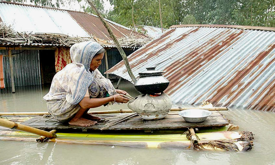 Cooking food on a makeshift raft as the flood engalfs her home In one of the rural area in Bangladesh,September 2007