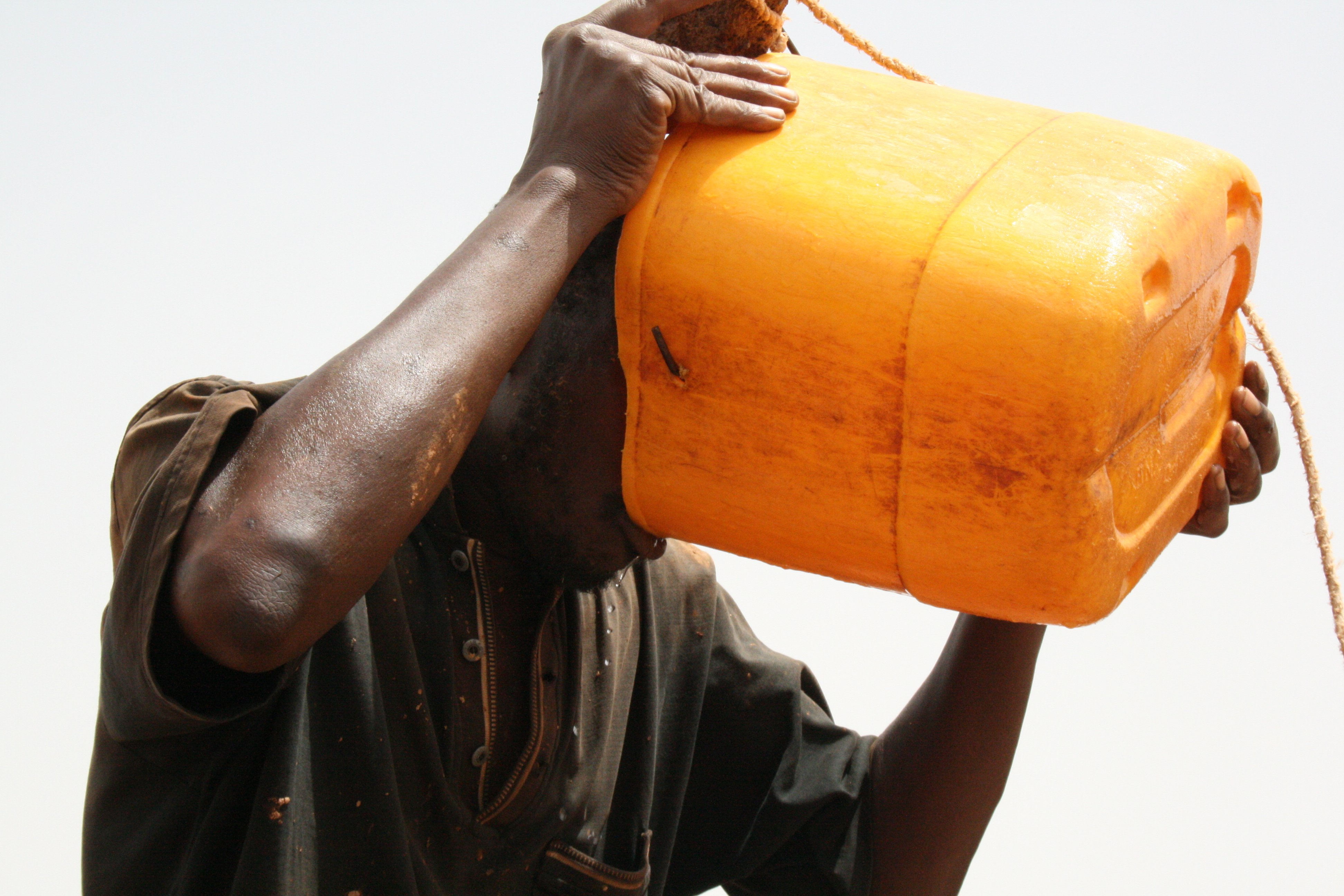 Man drinks water drawn from a home-made well in northern Burkina Faso.