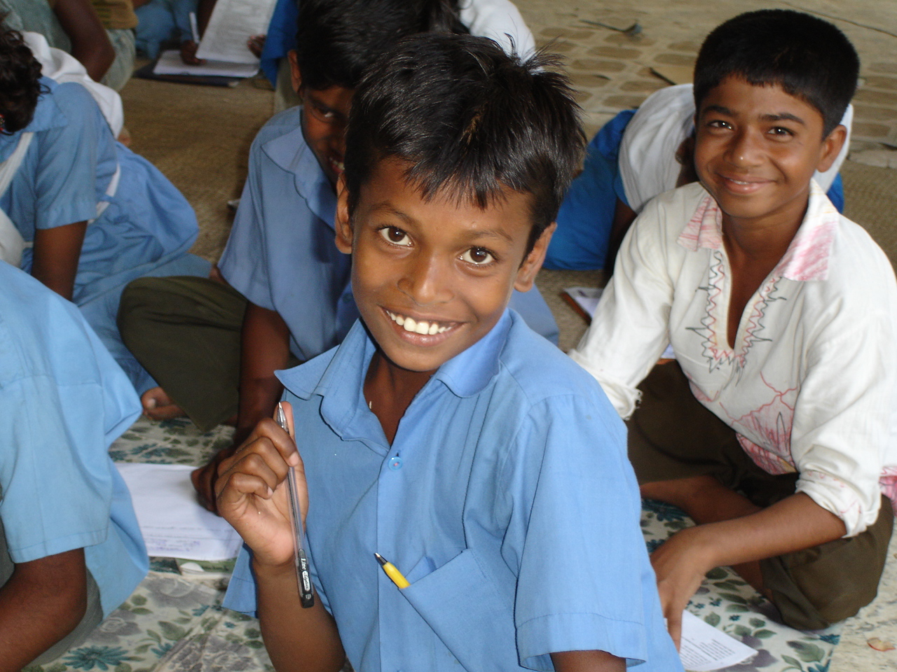 A young primary school student outside Dhaka smiles to the camera.