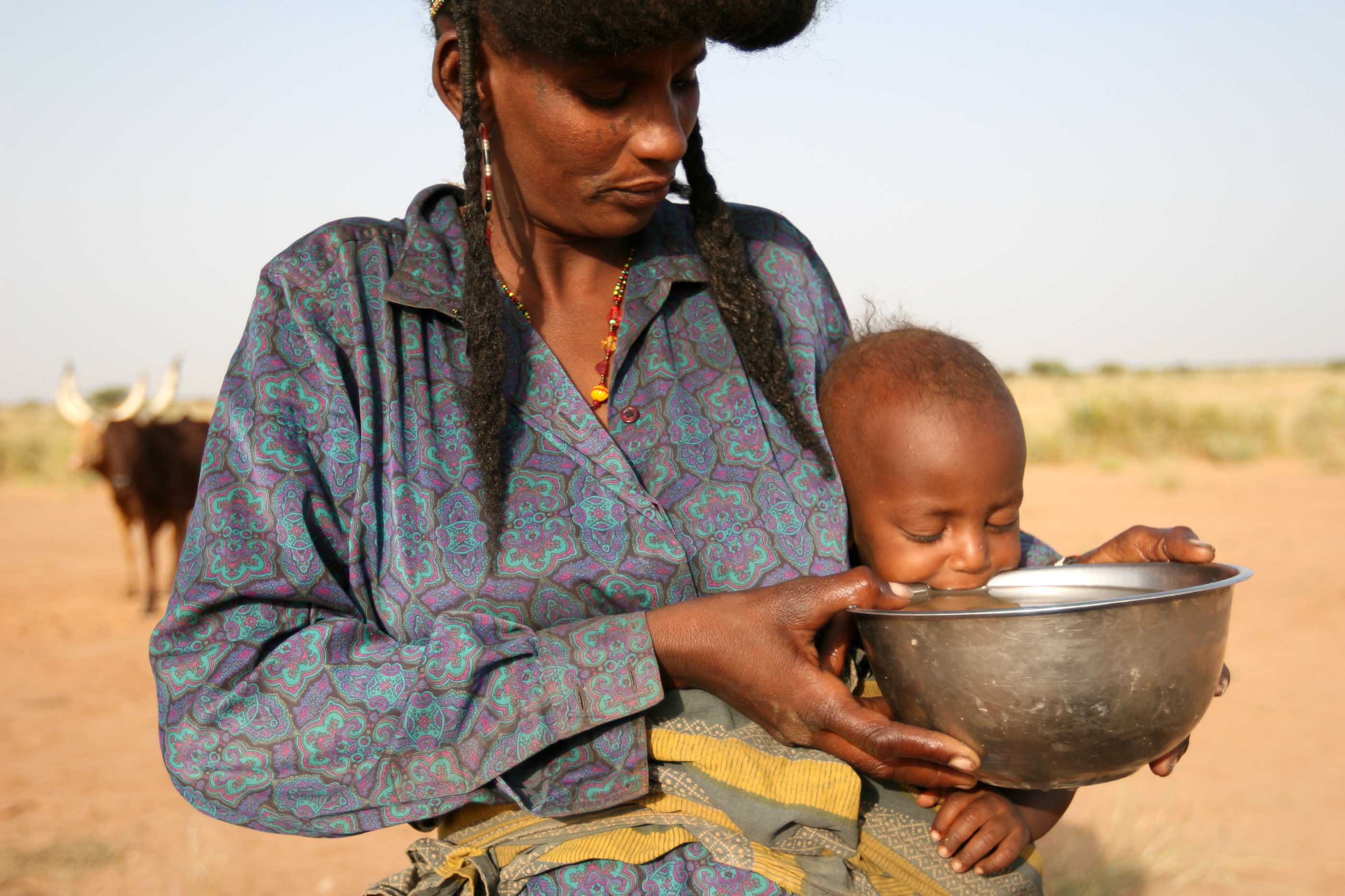A nomadic Wodaabe woman helps her baby drink water close to Ingall, northern Niger, 21 September 2007.