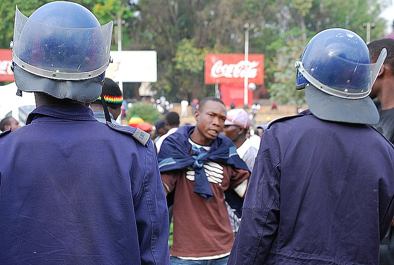 Zimbabwean riot police approach a man accused of jumping a queue to buy opaque beer in Harare.