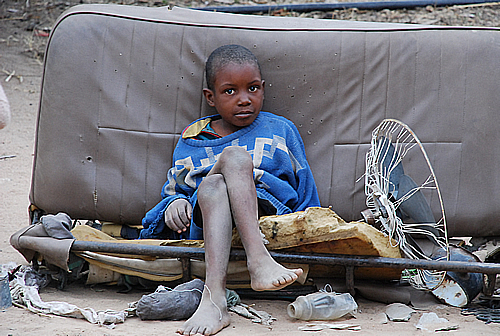 COMFORT ZONE: An HIV/AIDS orphan sits comfortably on a old bus seat in a rural home in Domboshava, Zimbabwe, November 2007.