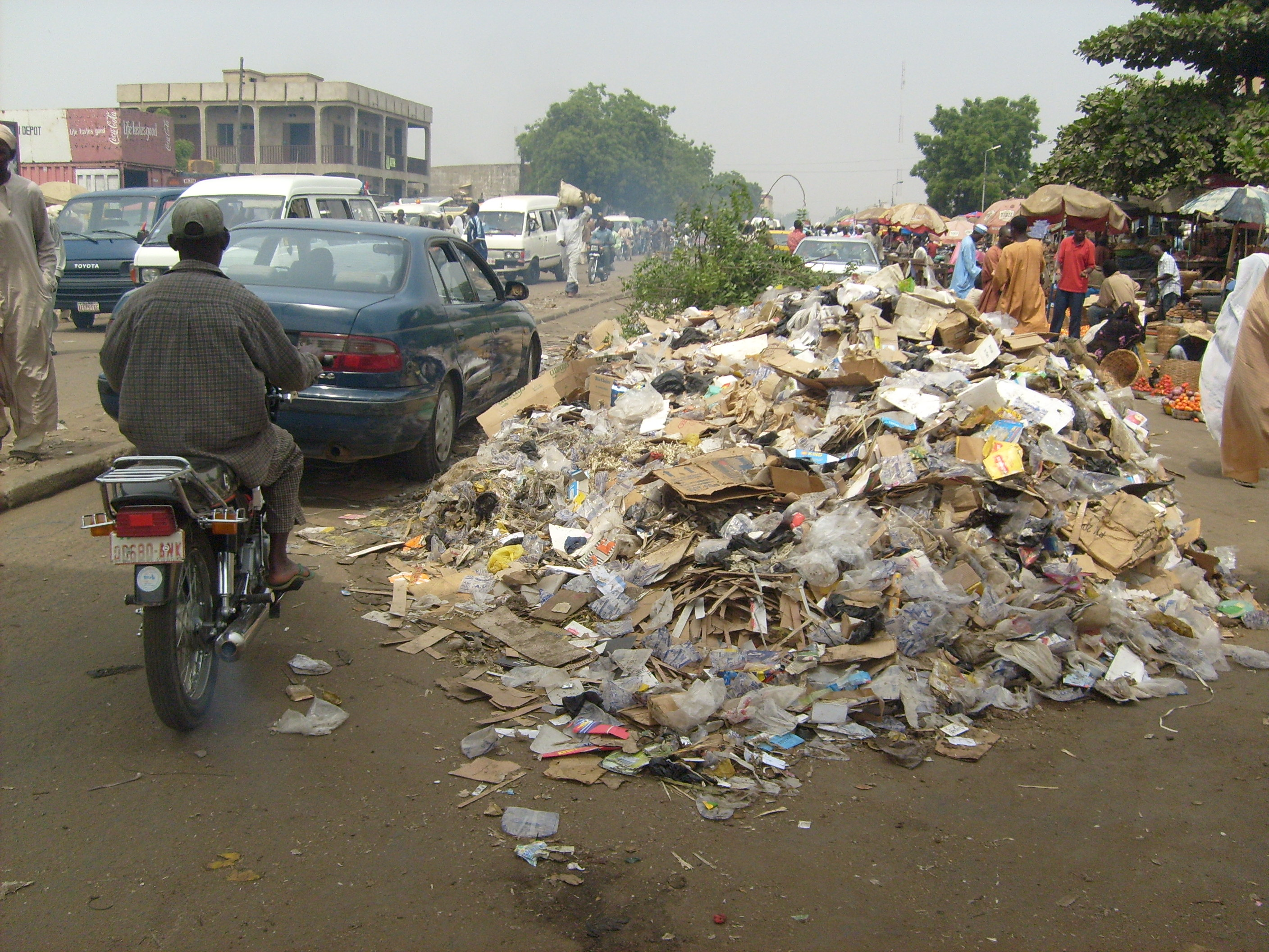 vehicles passing by a refuse heap that has taken over a part of the road on a Kano street.