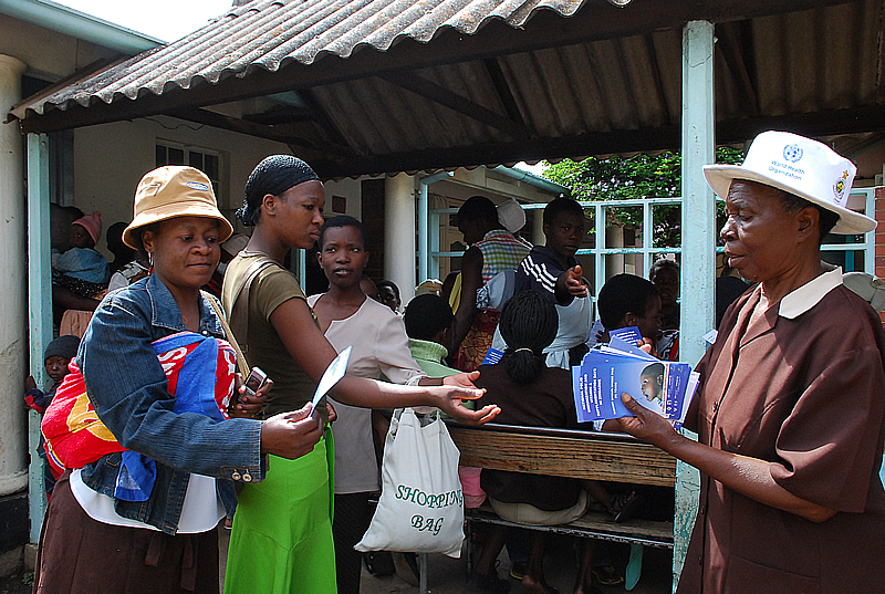 A health promotion worker from the City of Harare's Health Department distributes flyers with information on why children should be vaccinated. The Child Health Days (CHDs) are being co-ordinated by the Ministry of Health and Child Welfare in partnership