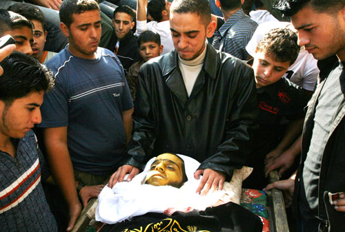 Relatives of Na'el al-Kurdi, 21, look at his body during his funeral in Gaza City on 17 November, 2007. Na'el, who suffered from cancer, died in Gaza after being unable to leave for medical treatment due to the closures imposed on the enclave.