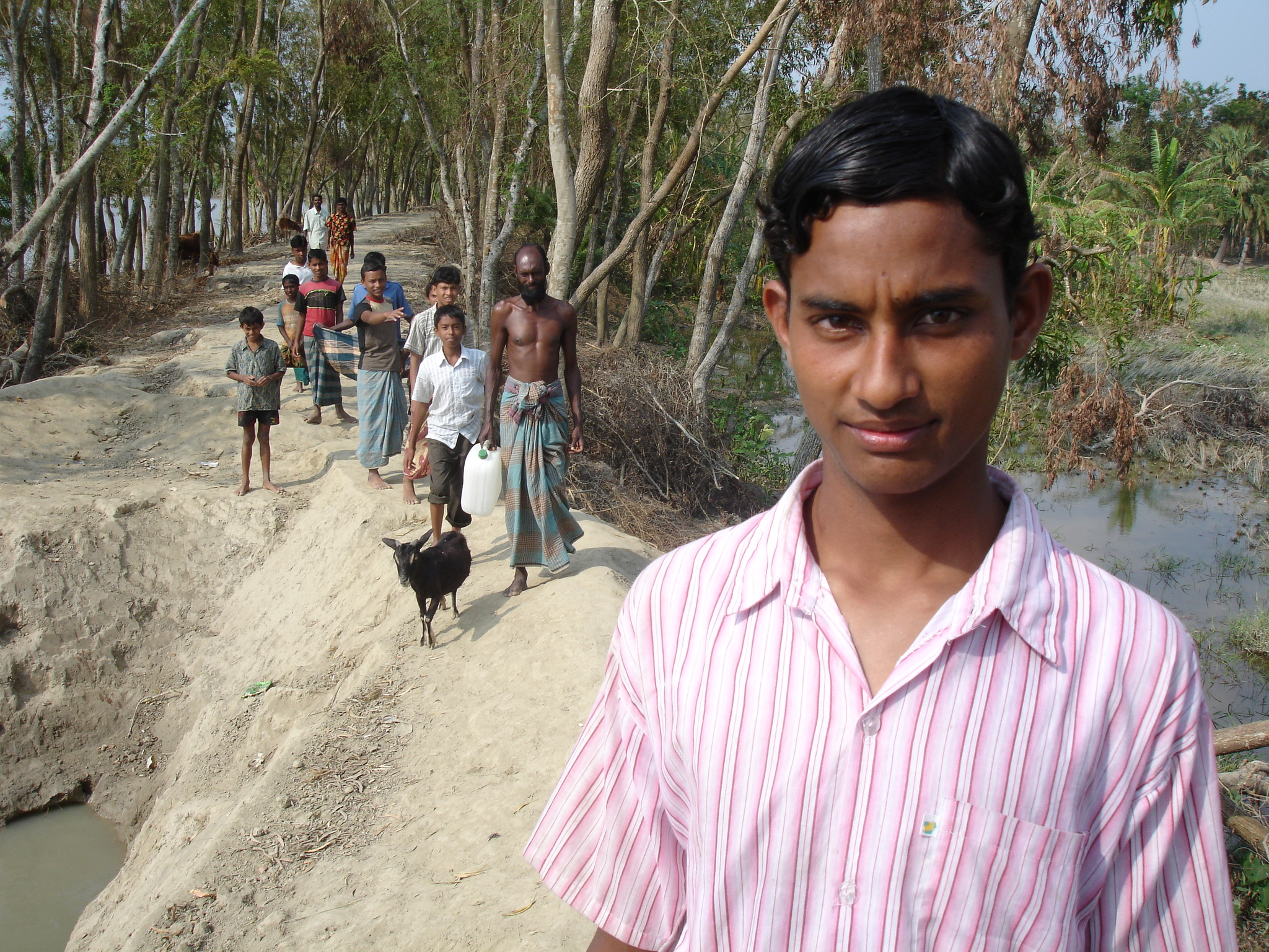 A young boy walks along a polder in Bangladesh's cyclone-affected Barguna District. Approximately 90 percent of area residents live within the confines of such polders, making them a critical first line of defense against tidal surges and cyclones.