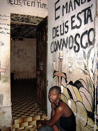 [Guinea-Bissau] An inmate sitting in the antechamber in front of his underground cell, 27 January 2007. The state of the cells is poor with no electricity, leaking pipes and graffiti. The prison was abandoned after the war of independence that ended in 19