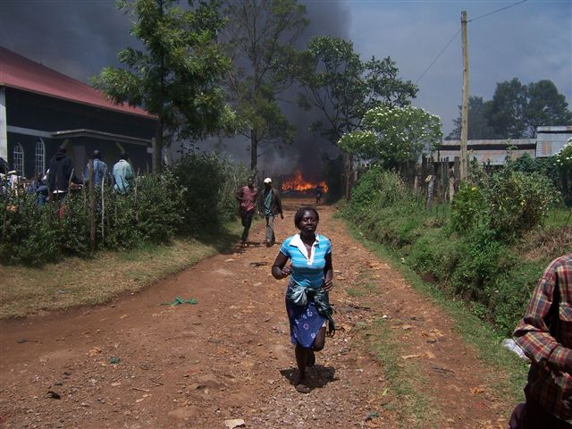 A woman runs from a fire started by opposition surporters during the on going post election violence in Kenya, Eldoret, Kenya. January 2008. Majority of people have been displaced following the post election violence that has been rampant in most parts of