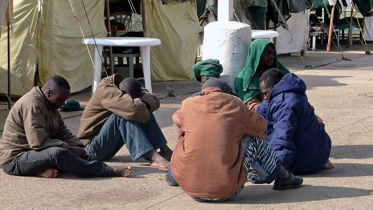 African refugees attempt to keep warm by huddling in the sunshine, at the tent compound for asylum seekers at Ktsiyot prison.