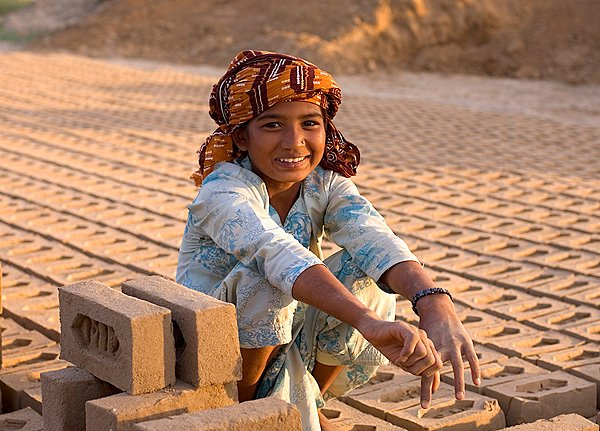 Thousands of children work as bonded labourers in Pakistan's brick kilns - their grins often disguising the hardship of the life they lead.
