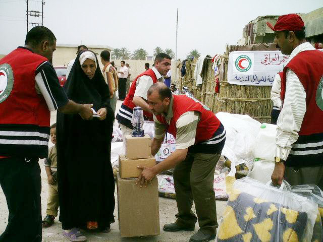 Iraqi Red Cresent Society staff hand out supplies to displaced families at al-Hashemite compound in Babil Province.