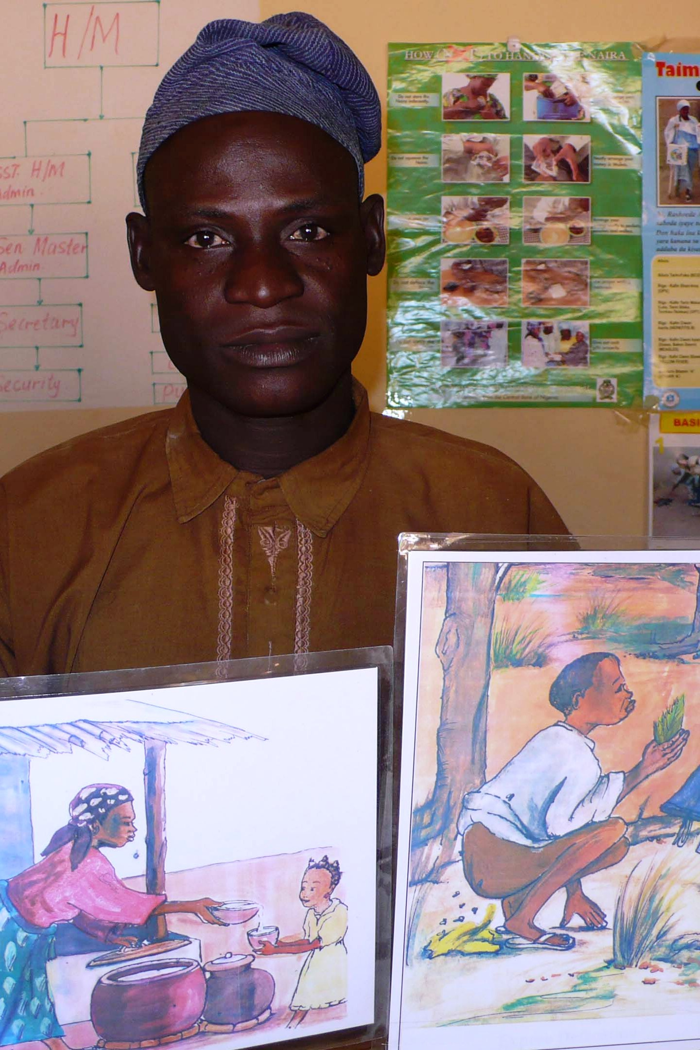 Sani Marafa, the headteacher for the Lokoto primary school shows drawings to raise awareness on the importance of using latrines.