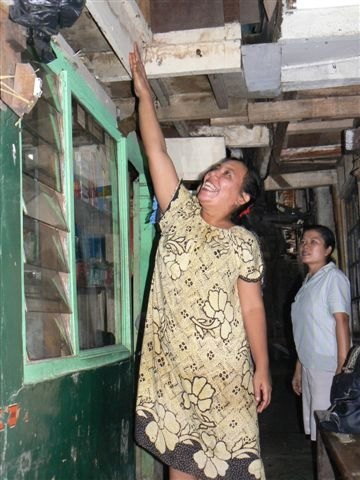Housewife Ratna Dewi shows how water reached the first floor of her house in this poor neighborhood in central Jakarta during recent floods.