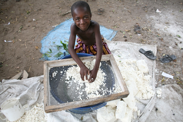 A young boy prepares cassava flour in the village of Foinda. Sierra Rutile area 250 km from Freetown, the capital city of Sierra Leone, February 2008. The people of Foinda village will soon be displaced due to expansion plans of Australian owned Sierra Ru
