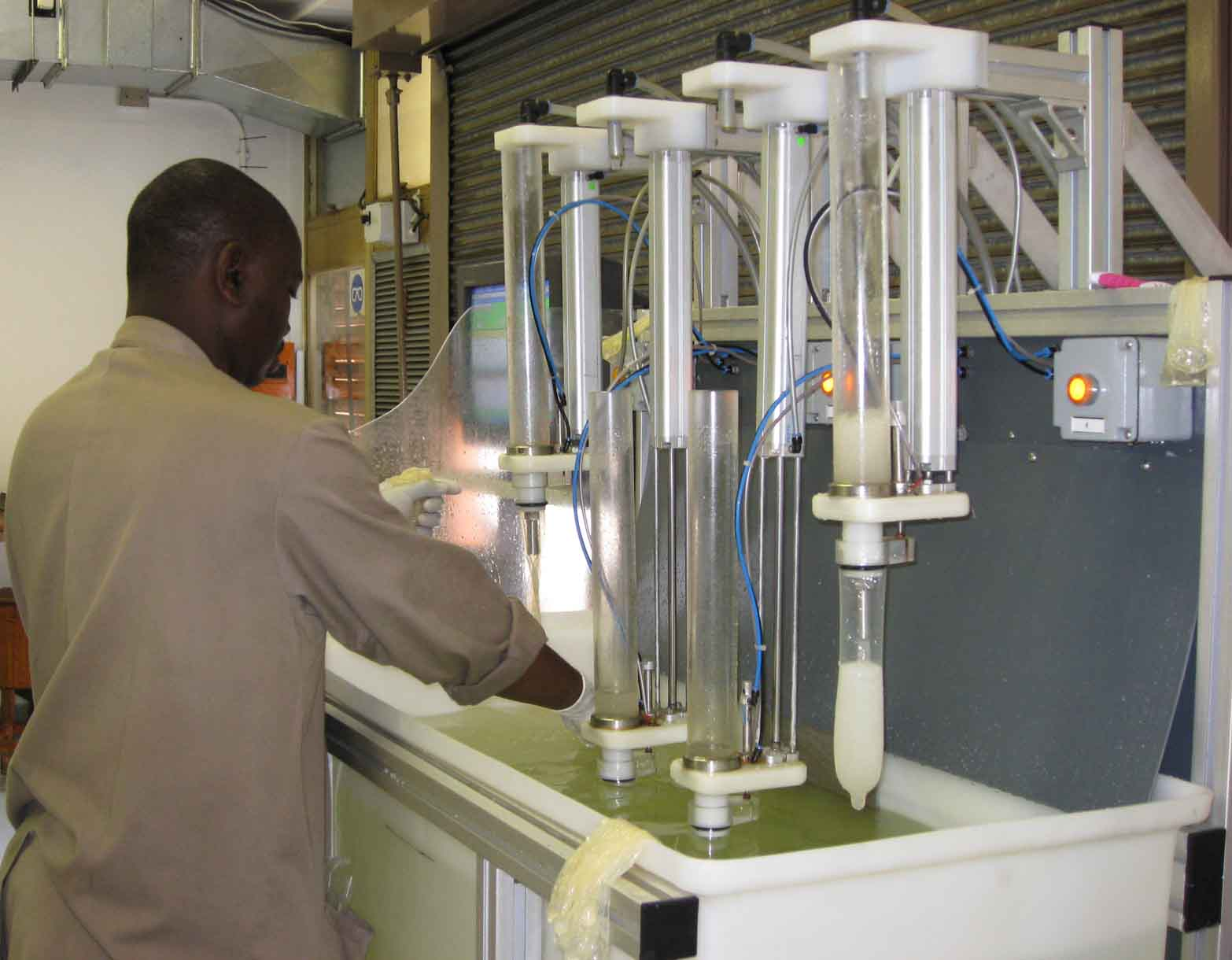 A testing officer at the South African Bureau of Standards puts condoms through one of the bureau's home-made testing machines to ensure condoms are free from holes.