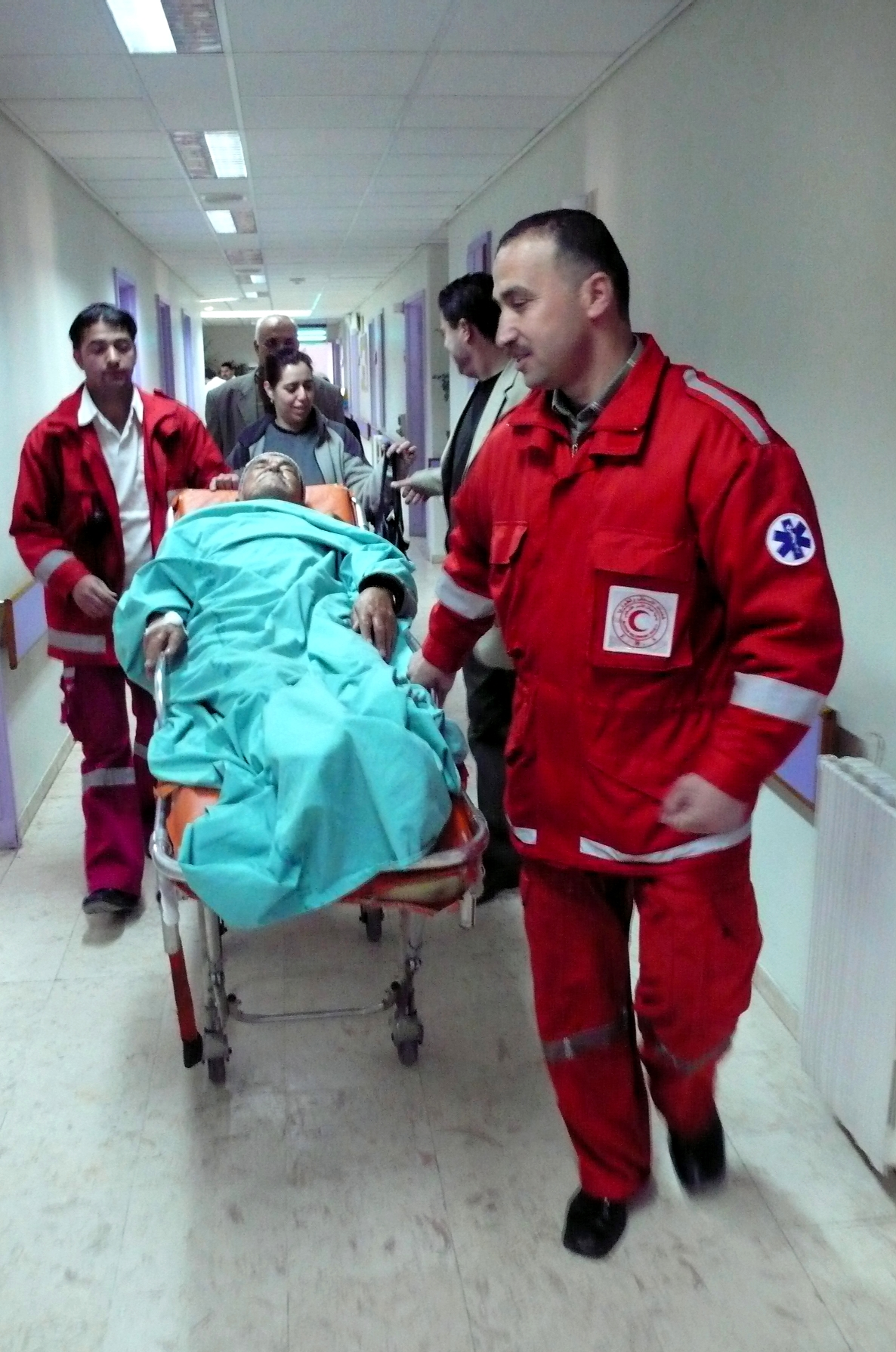 A patient is transferred by a Palestine Red Crescent team. The ICRC says that during conflict the main focus is keeping beds open for incoming trauma cases.