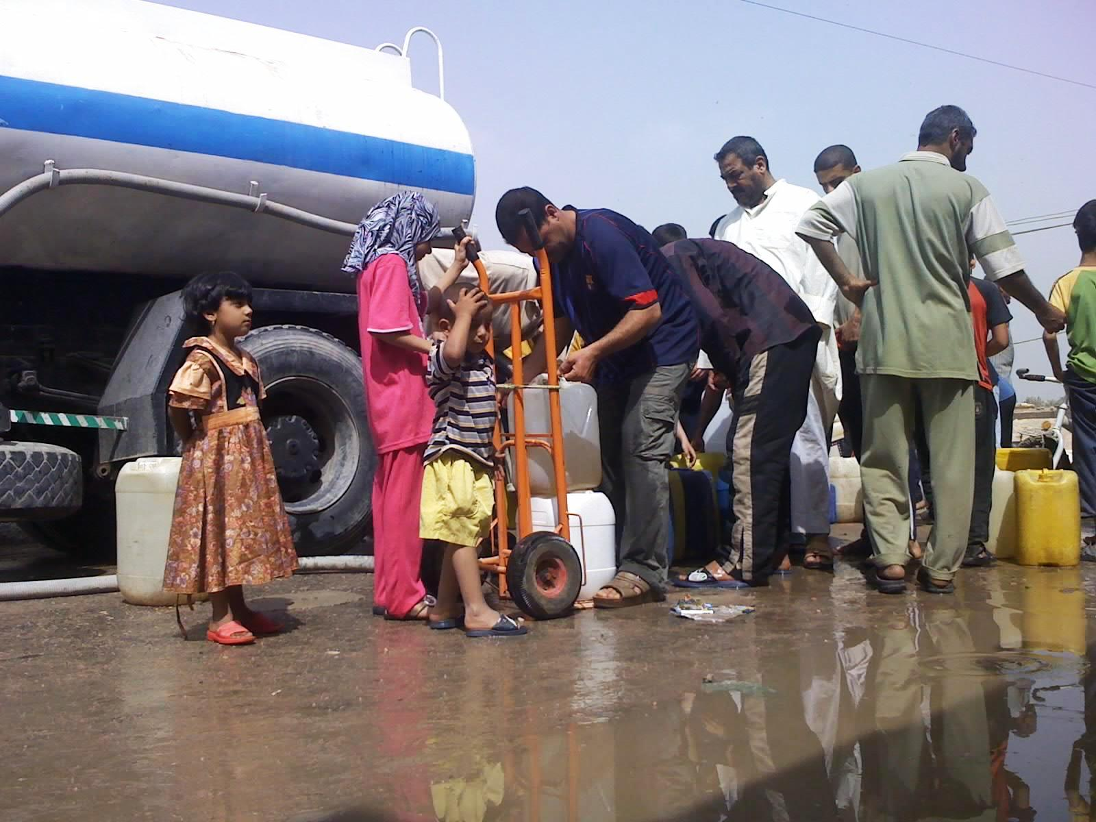 Basra residents rush to receive water from UNICEF water tanks.