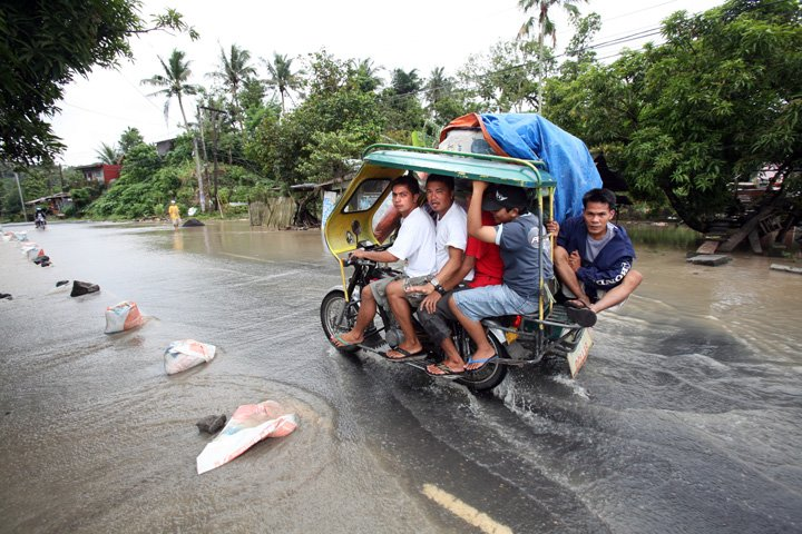 A public transport motorbike passes in a flooded road near Legazpi City, Albay Province, Bicol Region, the Philippines, March 2008. After six days of improving weather condition in Bicol, heavy rains spawned by a shallow low pressure area (LPA) again poun