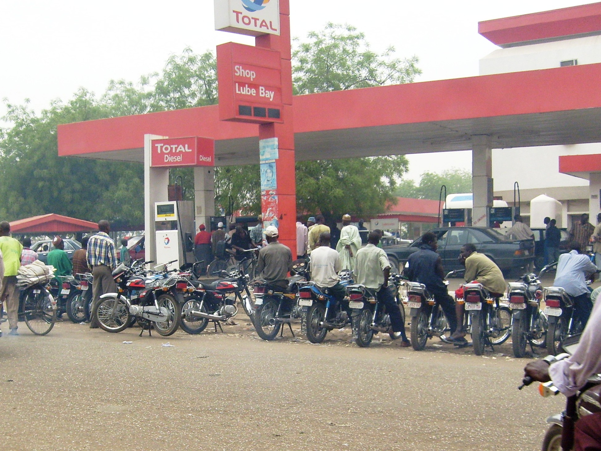 Motorcycle taxies known as 'Achabas' waiting for fuel in Kano but say many people say they can no longer afford the higher fares.